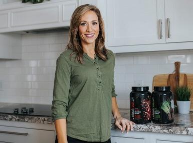 Lisa stood next to two tubs of IdealRaw protein
