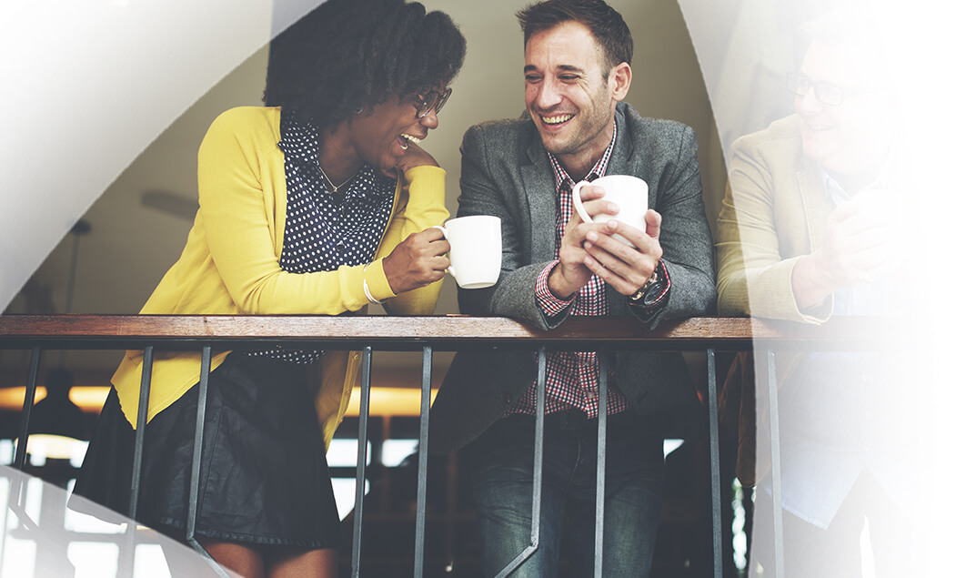 Young woman and man on their coffee break, laughing and smiling.
