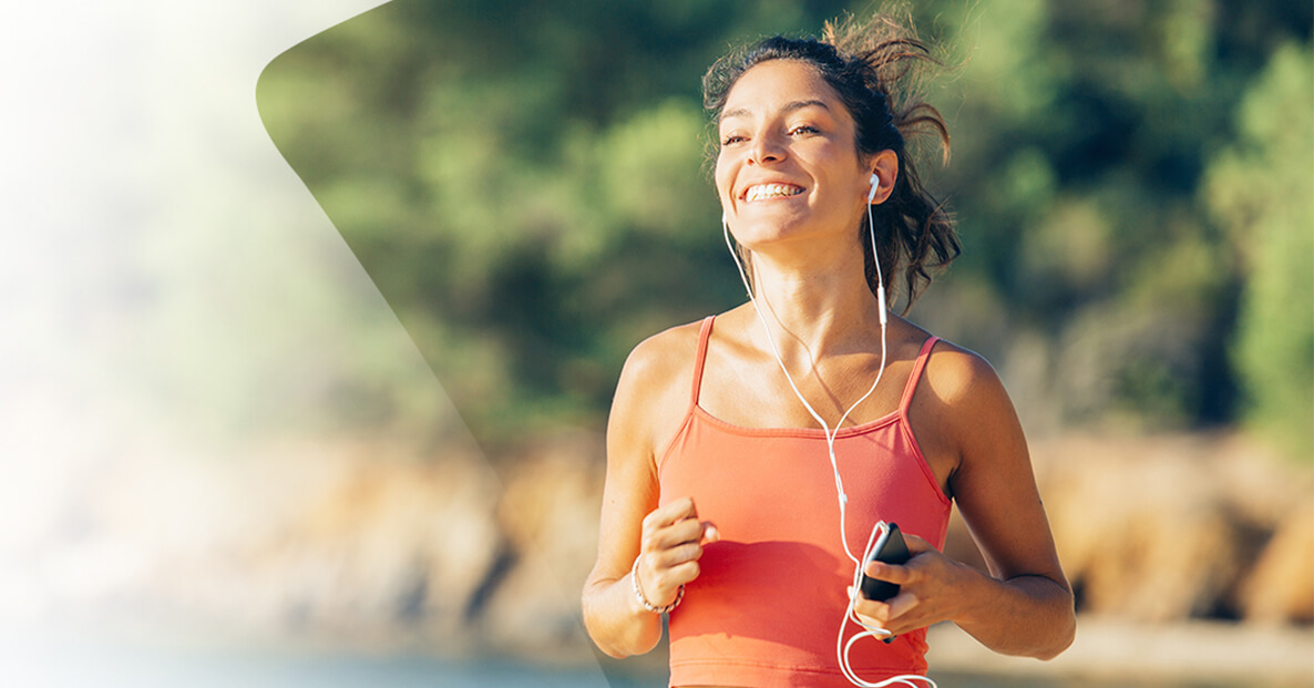 Woman running with headphones in and smiling to music.