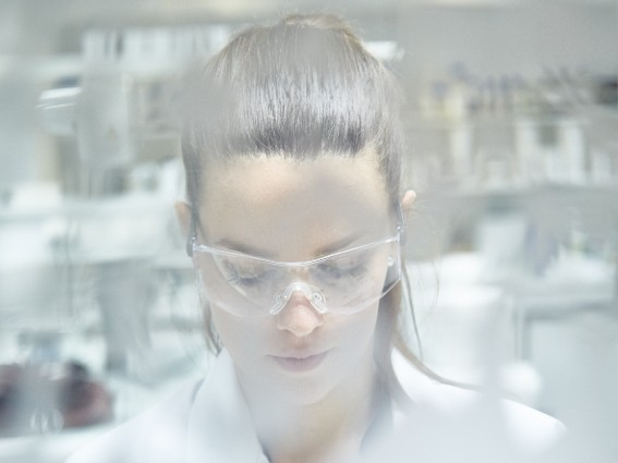 Female Scientist with goggles on formulating ingredients