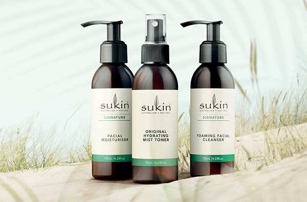 3 Sukin products on sand: Facial Moisturiser, Hydrating Mist Toner, Foaming Facial Cleanser