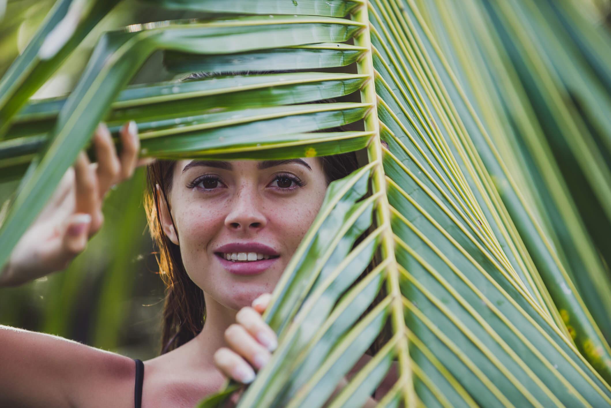 Woman peaking through a plant leaf