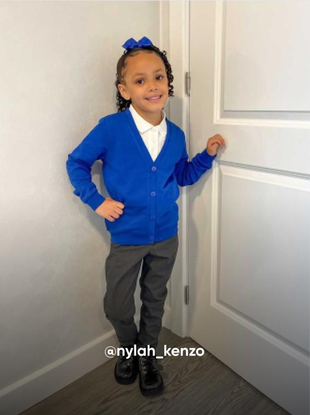 girl posting and smiling by a door - Visit Kickers Kids Instagram